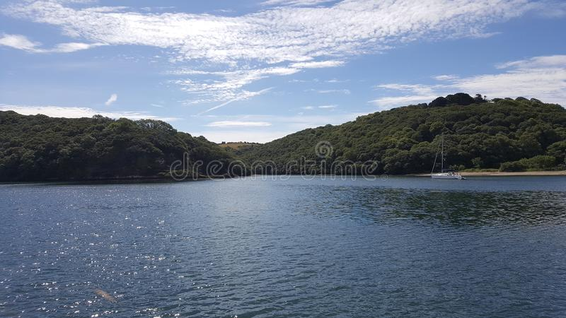 A day on the river. A scene shot from the river Fal in Falmouth, Cornwall. Blue sky and dark blue water. With green trees in the summer royalty free stock photos