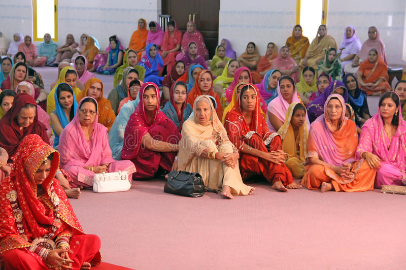 Scene at a Sikh Wedding. Guests at a Sikh wedding with the bride siting at the bottom left stock photo