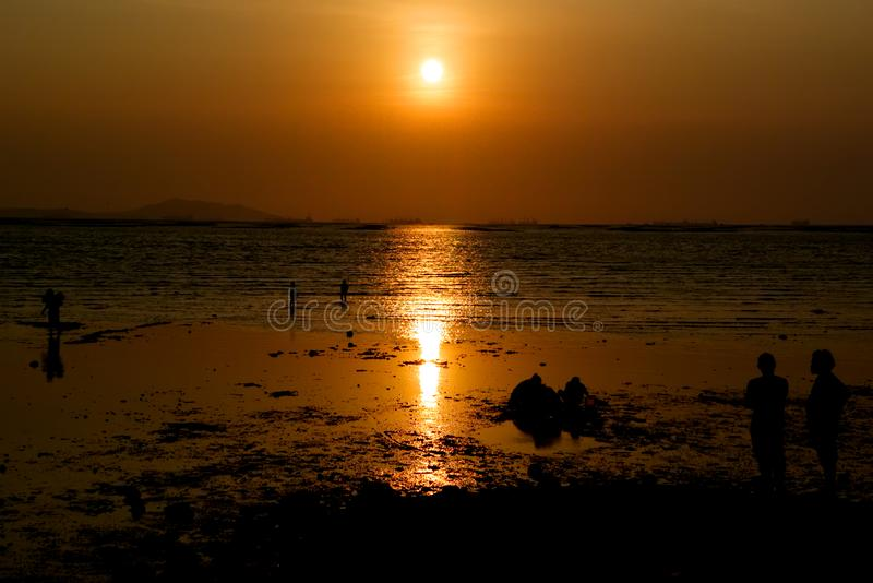 Scene of summer time, Silhouette people on beach with sunset sky. At sea stock image