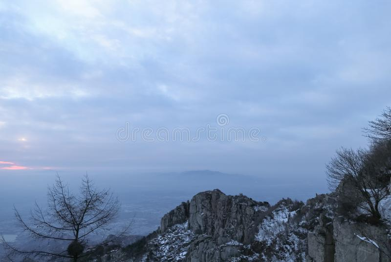 Rocks and snow on the peaks.Clouds wreathed it.The clouds in the sky were thick and heaving.Mountains piled up, clouds surging. This is the scene taken at the royalty free stock photos