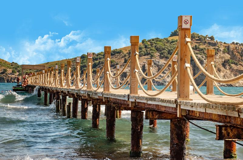 Concept holiday season vacation sea journey.Scene at Tropical Beach Resort with wooden pier and rope. View stock image