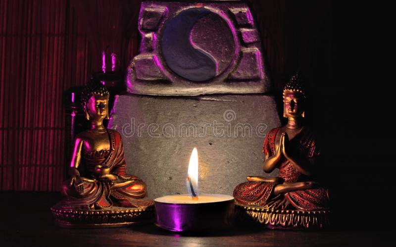 Scene: Two miniature Buddha statues, miniature altar and lighted candle,. 3D illustrations: low light, postcard royalty free stock photos