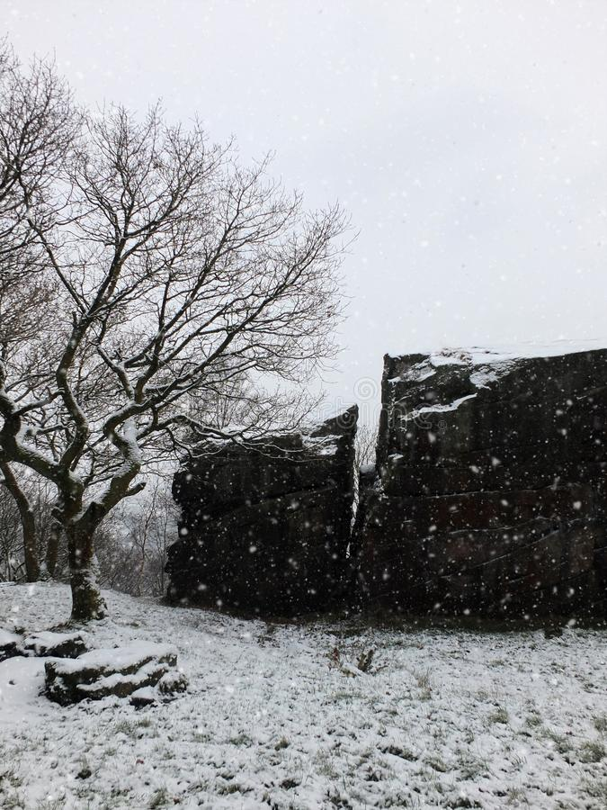 Scene with winter snow falling on a single tree and large rocky outcrop or boulder with path in west yorkshire england. Scene with winter snow falling on a royalty free stock image