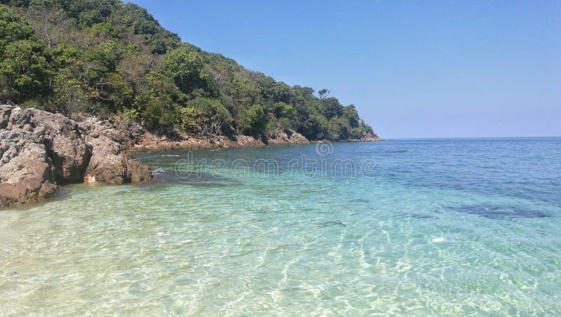 Sceneria jasna krystaliczna woda morska na plaży z wyspą tropikalny las, cieniem błękitny morze i niebieskim niebem, obraz stock