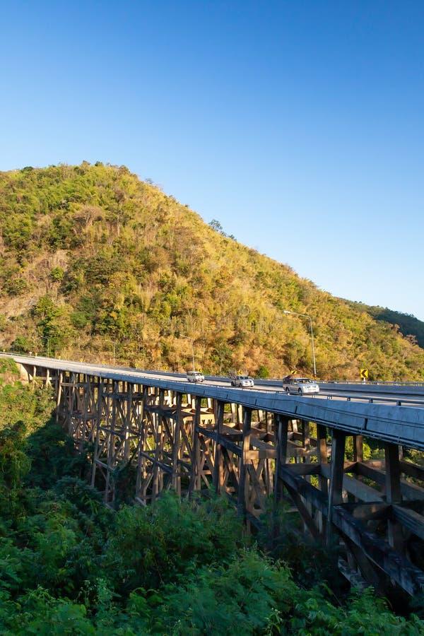 Sceneria niedźwiadkowy góra most przy półmrokiem, złoty zmierzch błyszczy na samochodu jeżdżeniu przez pasmo górskie i most fotografia stock