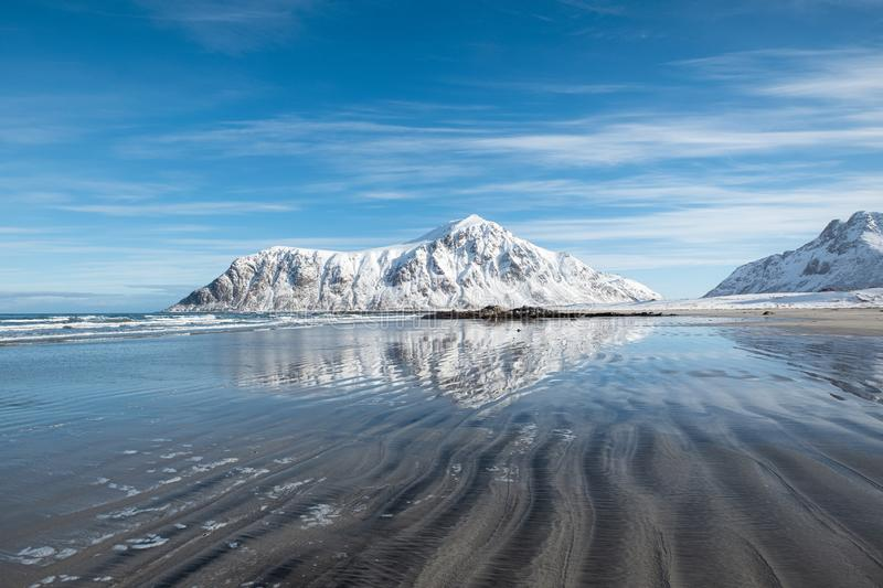 Scenery of furrow beach with snowy mountain on coastline at Skagsanden beach. Lofoten islands, Norway stock photography
