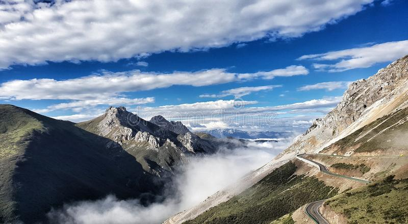 The scenery between going to Yachen Gar, Sichuan China in June 2019. The combination of the nature with blue sky, mist and mountain to be naturally heritage stock photo