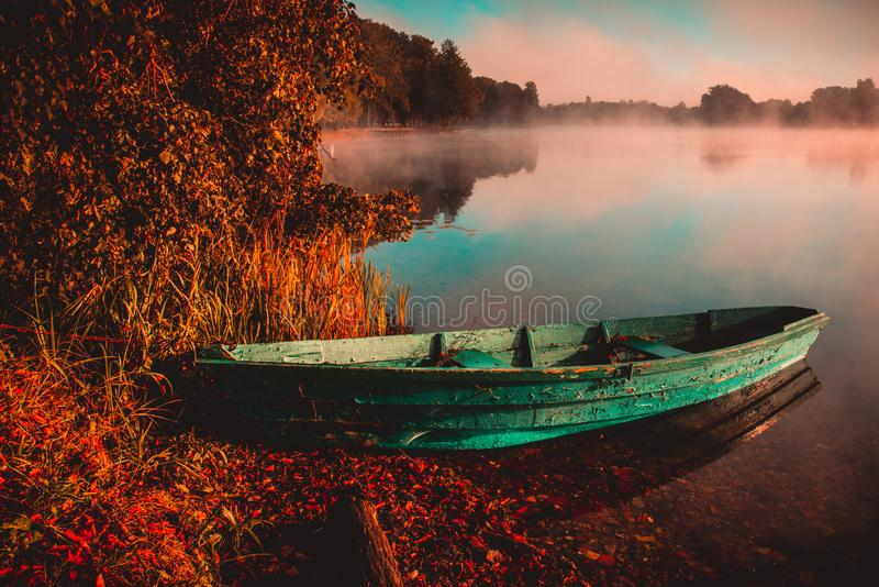 Scenery of lake with old boat in water. Misty colorful autumn morning stock photos
