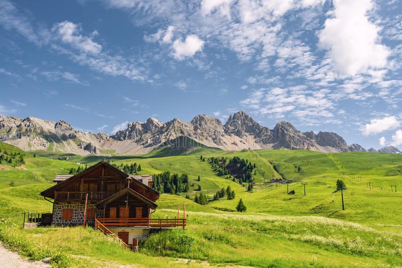 Scenery landscape with house on green field near mountain. Idyllic Alps with wooden house on green field near high rocky mountain under blue sky stock photos