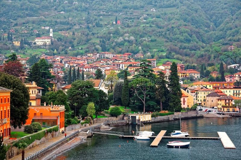 Scenery of Lenno in Lombardy Italy, a lakeside town by Lago di Como with view of ferry boats parking by the dock. Beautiful houses along lakeshore & Abbazia stock images