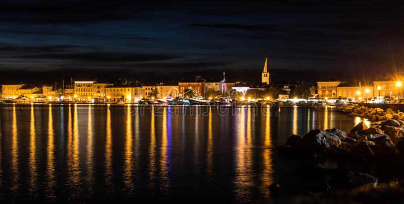 Scenery of night illumination reflecting in water surface in the dark. royalty free stock photos