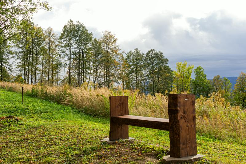 Scenery panorama in sunny day with view on mountains, green forest, meadow, blue sky and white clouds and with a bench for rest in royalty free stock image