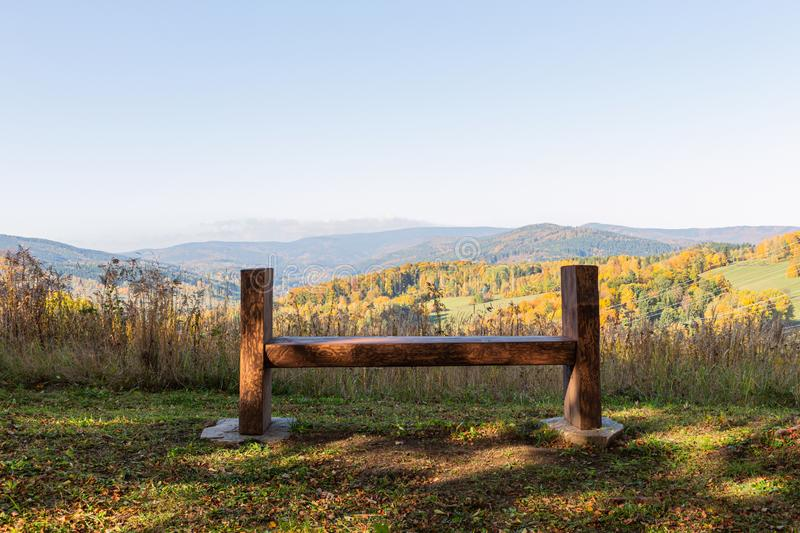 Scenery panorama in sunny day with view on mountains, green forest, meadow, blue sky and white clouds and with a bench for rest in stock image