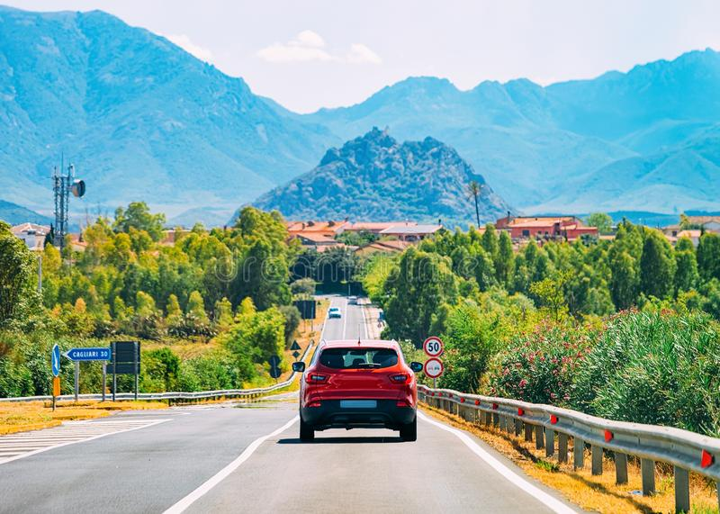 Scenery with red car on highway in Cagliari Sardinia hills royalty free stock images