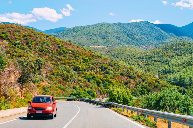 Scenery with red car in highway in Cagliari Sardinia hills royalty free stock photography