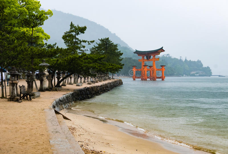 Scenery of sea coast on Miyajima Island. Viewing the famous orange floating Japanese shinto gate & x28;Torii& x29; of Itsukushima shrine in the bay stock photography