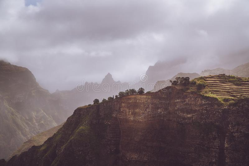 Scenery with shape of huge rocks and motion clouds mist on sky. Surreal moment before a thunderstorm in the mountains on stock image