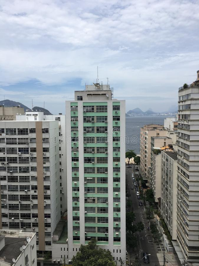 Scenery of skyscrapers under a cloudy sky with the beach in Rio De Janeiro on the background stock photography