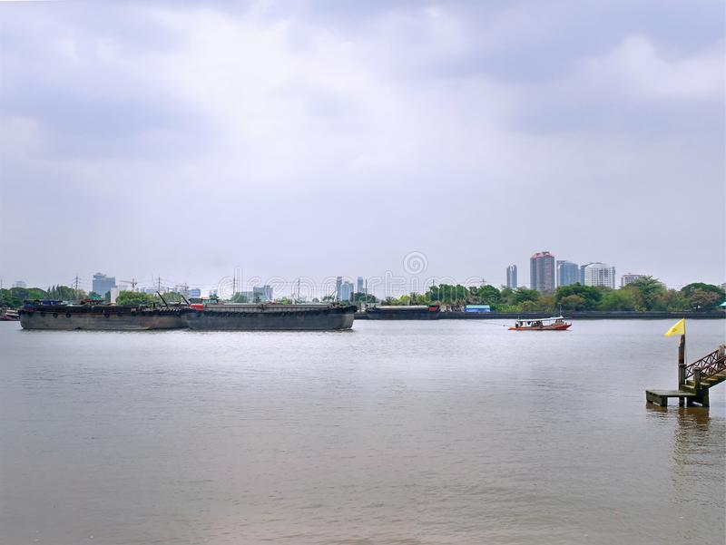 Scenery of Small Tug Boat Towing Large Barge Ship in the River. Tranquil Scenery of Small Tug Boat Towing Large Barge Ship in the River stock photo
