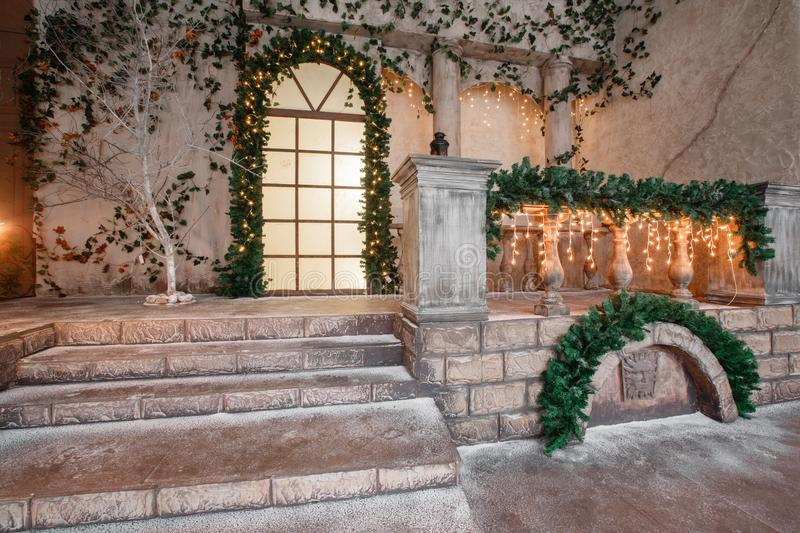 The scenery of the Studio or theater. Entrance in an old architecture with staircase and columns. Christmas decoration. With garlands and fir branches stock images