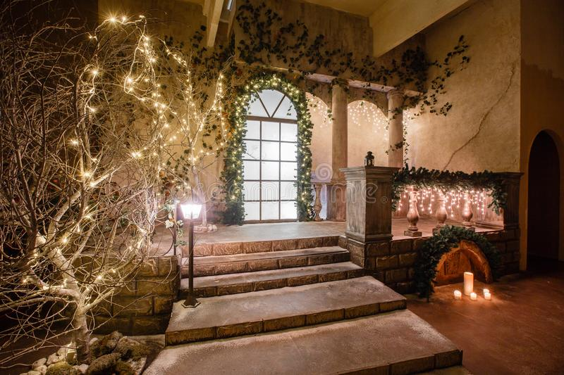 The scenery of the Studio or theater. Entrance in an old architecture with staircase and columns. Christmas decoration. With garlands and fir branches stock image