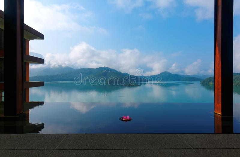 Scenery of Sun Moon Lake, a famous tourist destination in Nantou, Taiwan. With a lotus flower on an infinity pool & foggy mountains in background reflected on royalty free stock photos