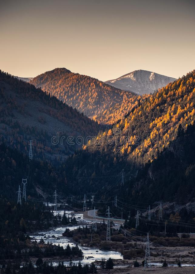 Scenery sunrise on mountain with electric poles and river in autumn stock images