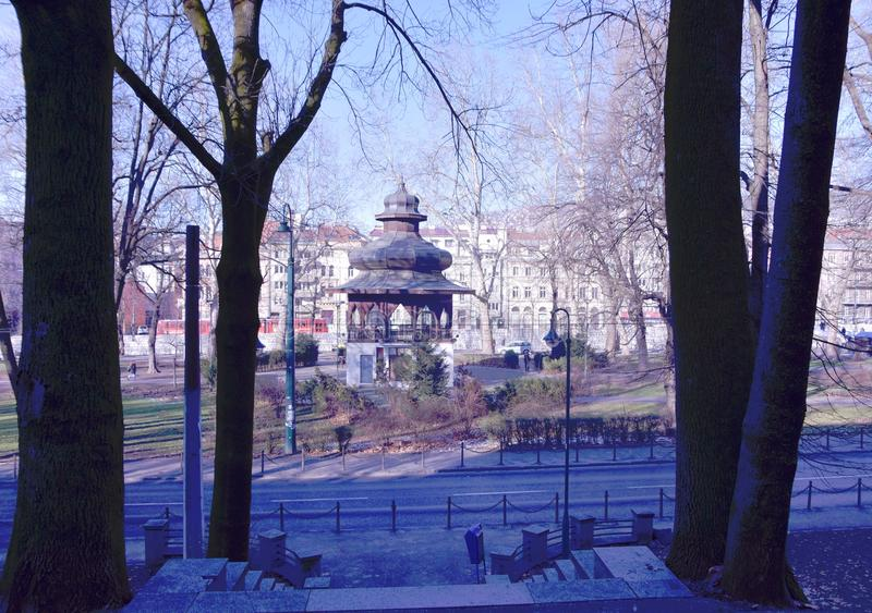 Image of oriental looking structure building in the city park with view of trees and street. Scenery view of oriental looking structure building in the city park stock photo