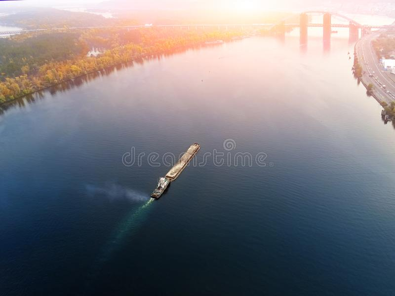 Scenic aerial cityscape of Kiev and river Dnipro at sunset. Tugboat supporting barge with sand bulk materials heading down river. Dnieper. Ukrainian inland stock photos