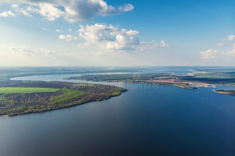 Scenic aerial panoramic landscape of Oskol river curve in eastern Europe with green forest at banks and blue cloudy sky. Natural royalty free stock photo
