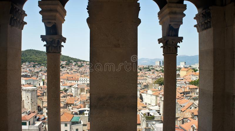 Scenic aerial view of the city through stone window from the bell tower, roofs of houses in old town, beautiful cityscape, sunny stock photos