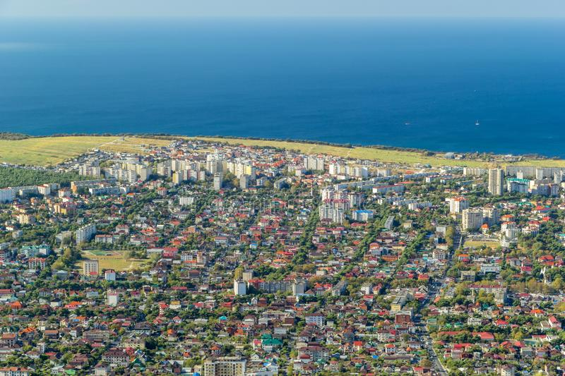 Scenic aerial view of Gelendzhik resort city district and Black sea coastline. Sunny day. Buildings, boats in Black sea, horizon and skyline in frame. Photo of stock photography