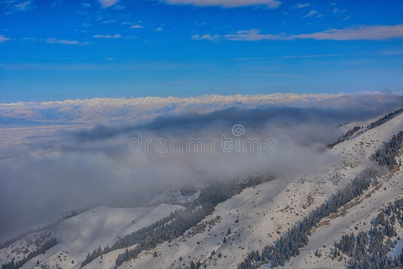 Scenic alpine landscape with fog . under mountains, forest and blue sky. National park of Kyrgyzstan. Nice view royalty free stock images