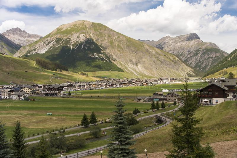Scenic alpine landscape with town and chalets. In the Italian alps at Livigno, Lombardy nestling in a valley below high alpine mountain peaks stock photography