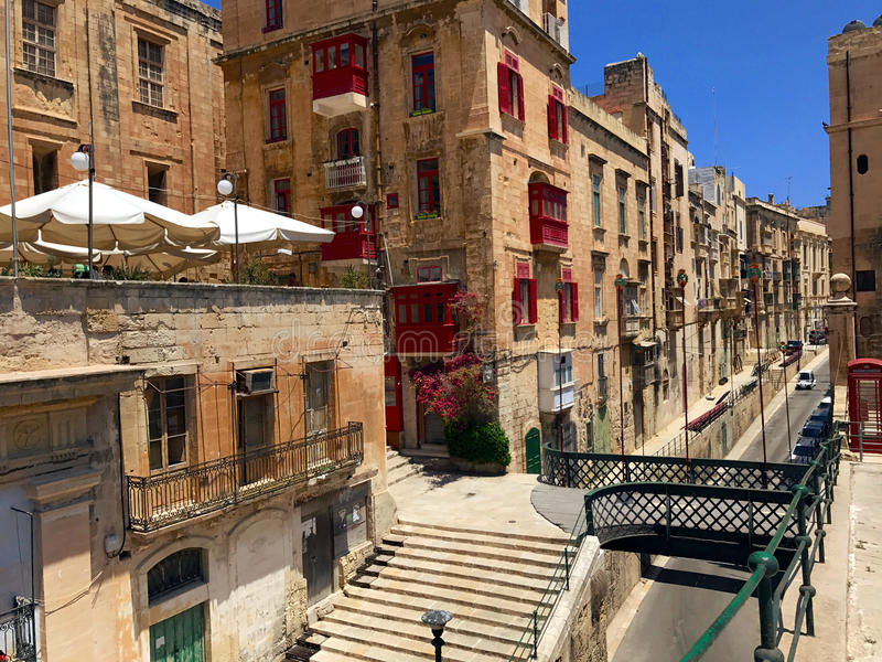 Scenic ancient Valletta Streets of Malta. Bridges, scenic streetview of the ancient city of Valletta, a UNESCO World Heritage City. Red windowsills and tents of royalty free stock image