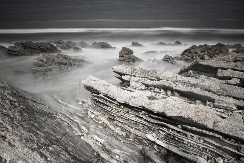 Scenic atlantic coastline with waves in motion around rocks on sandy beach in long exposure, bidart, basque country, france. In black and white royalty free stock images