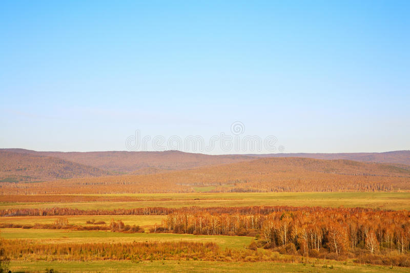 Scenic autumn landscape. meadow, forest and mountains royalty free stock photos