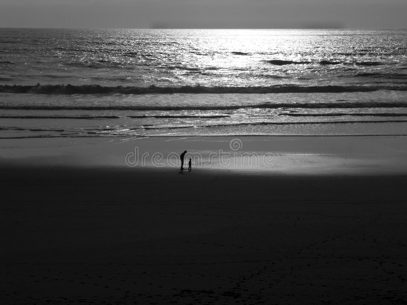 Scenic beach at sunset. Scenic view of sandy beach at sunset with parent and child silhouetted by sea royalty free stock photos
