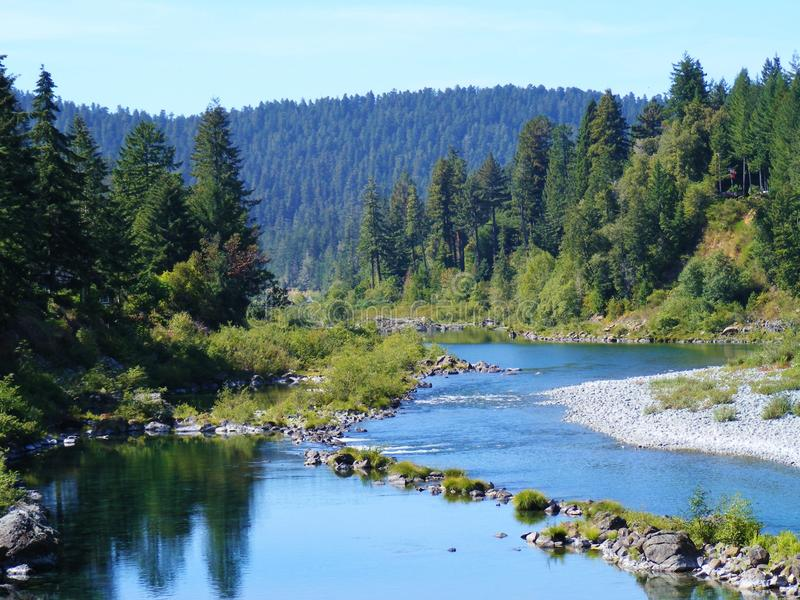 SCENIC BLUE TWISTING OREGON RIVER. I drove around a curvy road in Oregon to this lovely scene. The bright blue river was winding and twisting around this stock photos
