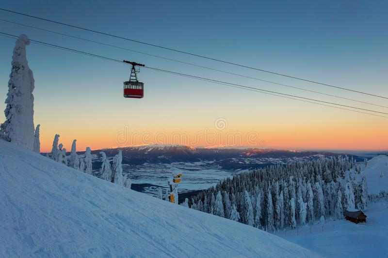 A scenic cable car flying over a piste in Poiana Brasov, Romania winter & ski resort with a view of landscape ice trees or snow royalty free stock photo