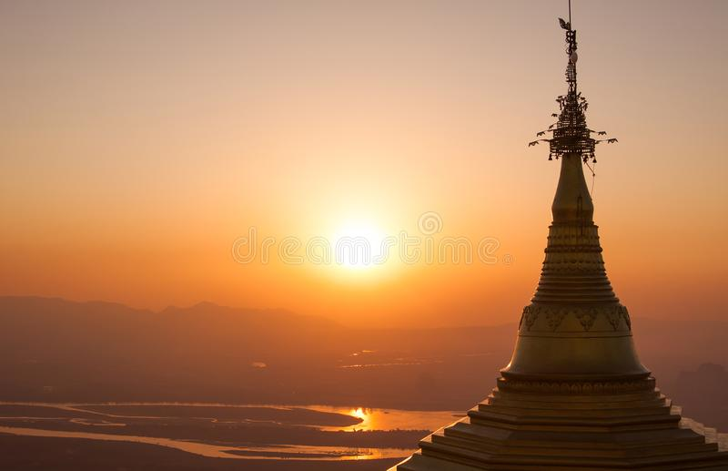 Scenic close up view of golden ancient buddhist stupa on peak of sacred mountain in colorful sunset light. royalty free stock photo