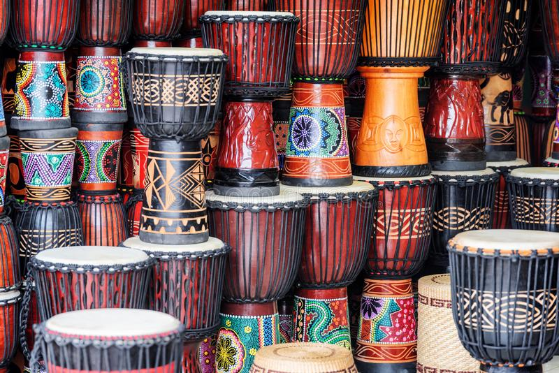 Scenic colorful rows of wooden djembe drums at souvenir shop. Fenghuang, China - September 22, 2017: Scenic colorful rows of wooden djembe drums at souvenir shop stock images