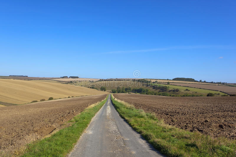 Scenic country highway. A scenic country highway through cultivated hillside farmland in the yorkshire wolds england stock photos