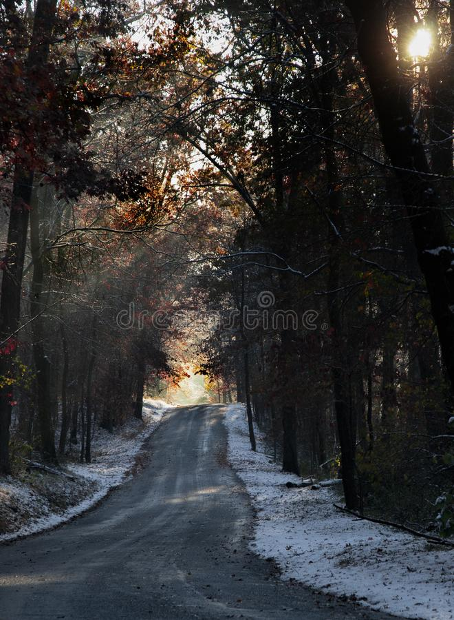 Country road in Maryland with snow covered road and sun shinning through tress. Scenic country road in Maryland with snow covered road and sun shinning through stock image
