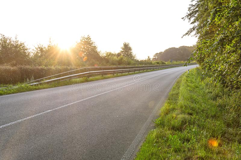 Scenic country road at sunrise with lens flare. Scenic country highway at sunrise with lens flare stock images