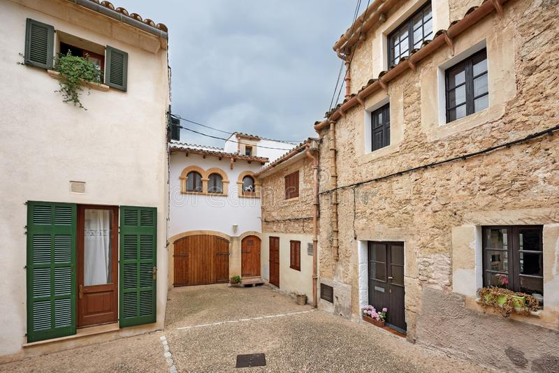 Scenic courtyard in old residential neighborhood. Village Capdepera, island Majorca, Spain. Scenic courtyard in the residential neighborhood on a cloudy summer royalty free stock photography