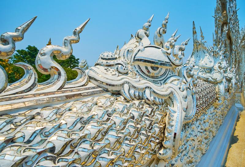 Naga serpents on Bridge of Rebirth Cycle, White Temple, Chiang Rai, Thailand. The scenic detail of Rebirth Cycle Bridge with carved stucco Naga Nagar, Nayar stock image