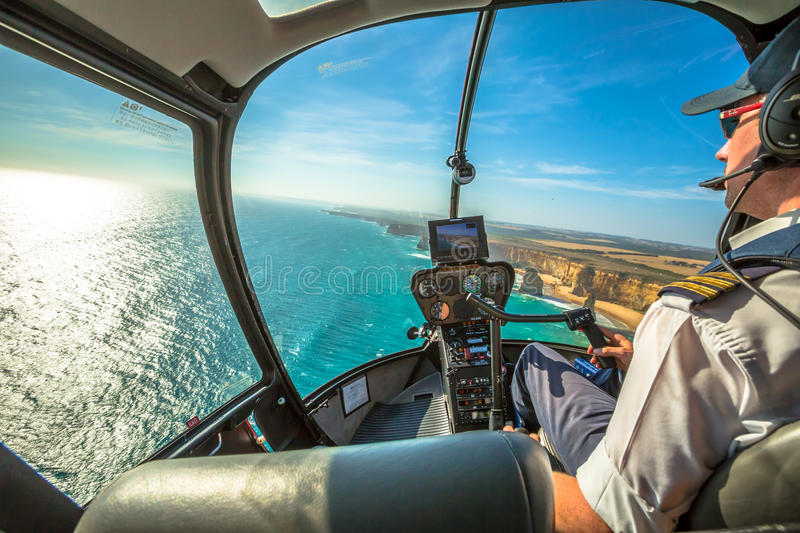 Twelve Apostles scenic flight. Closeup of the cockpit of a helicopter and its pilot who performs a scenic flight over the Great Ocean Road in Victoria, Australia stock image