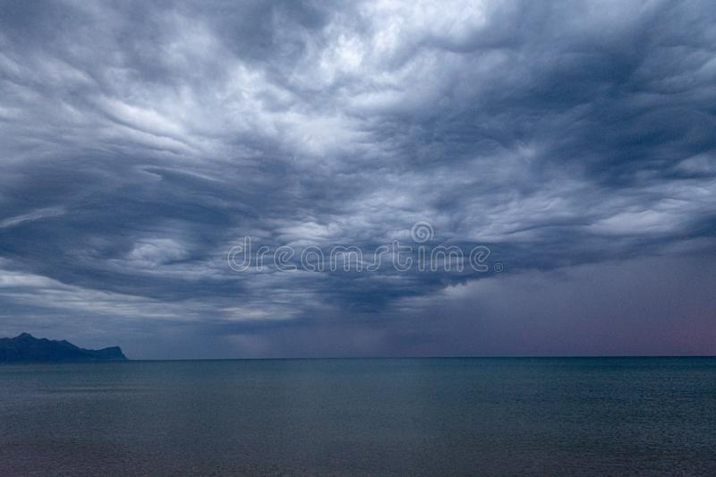 Scenic gray-blue clouds during sunrise over coastline with sandy beach and clear sea water in Alcamo Marina, small town in Sicily. Scenic gray-blue clouds during stock photo