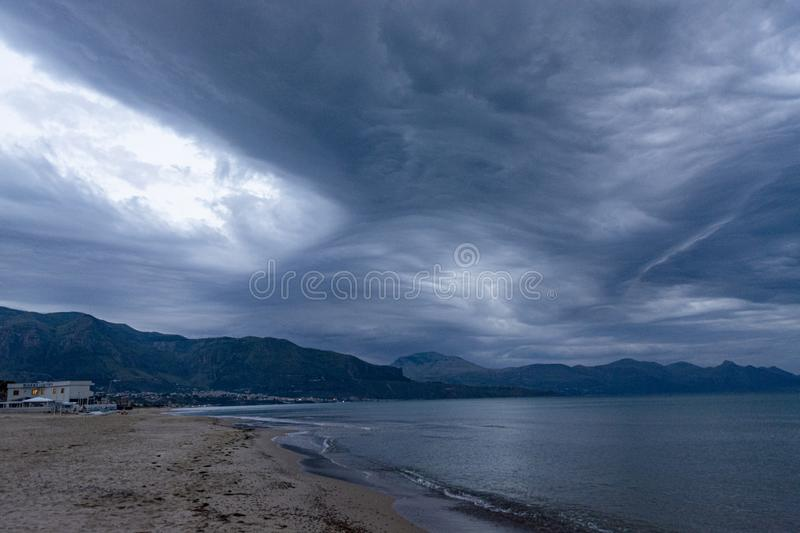 Scenic gray-blue clouds during sunrise over coastline with sandy beach and clear sea water in Alcamo Marina, small town in Sicily. Scenic gray-blue clouds during stock images